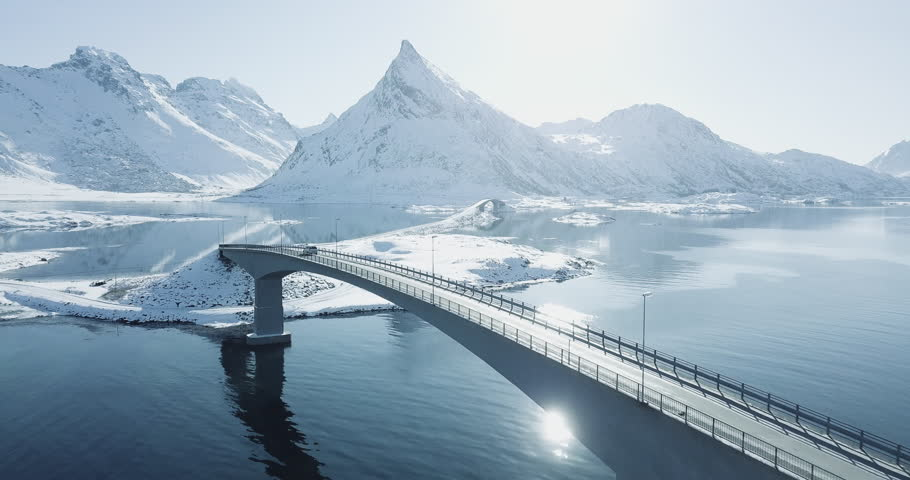 Aerial drone footage of amazing arctic Lofoten Islands winter wonderland scenery with car passing bridge on a beautiful cold sunny day, Fredvang, Lofoten archipelago, Norway, Scandinavia.
