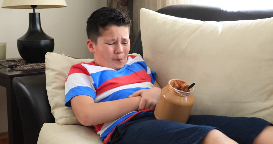 Painful child having abdominal pain, eating too much peanut butter at home | Shutterstock HD Video #1010018876