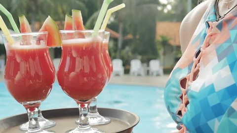 Summer pool party. Close up of fresh juice. Girl with a tray and glasses with smoothie. Happy group of young friends enjoying the natural drinks together in the resort. Healthy lifestyle.