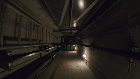 In a dark elevator shaft, the cabin moves up. The ride goes through the 5 floors of the house.