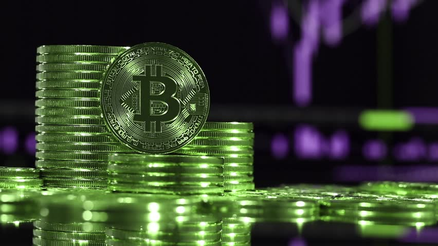 Crypto currency Gold Bitcoin, BTC, Bit coins rotates. Block chain technology, Bitcoin mining concept in green style, monitor with financial charts at background | Shutterstock HD Video #1010085686
