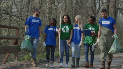 Multiethnic people in group of volunteer community walking in row wearing colorful t-shirts and talking to coordinator.