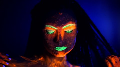 Fashion sexy dancer with braids in neon light. Fluorescent makeup glowing under ultraviolet light. Night club, party, halloween psychedelic concepts. Mysterious woman with UV painting