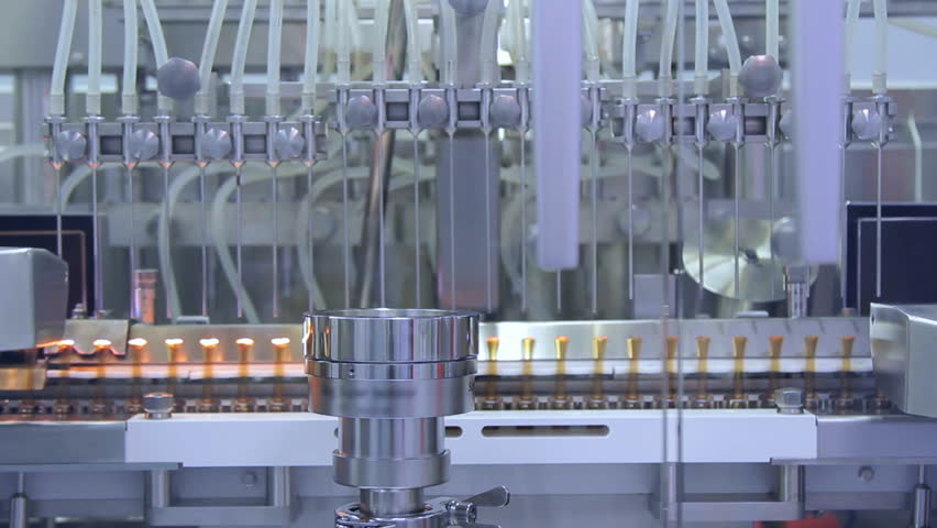 Pharmaceutical manufacturing equipment. Pharmaceutical manufacturing machine at medical factory. Pharmaceutical technology concept. Medical ampoules on automated production line
