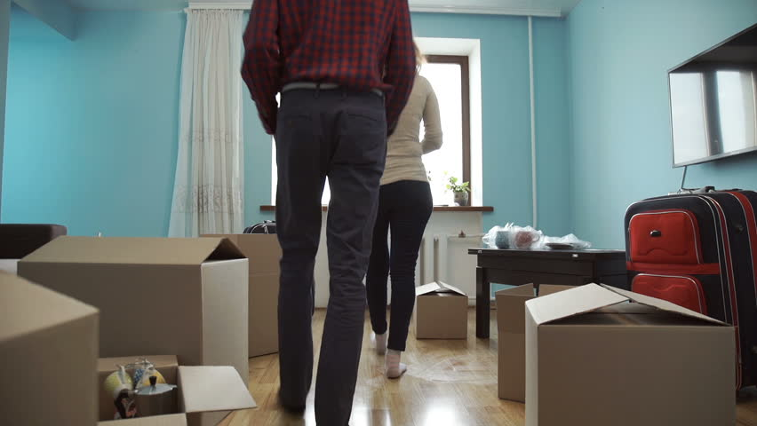 Young couple collects things in a box for moving to a new apartment | Shutterstock HD Video #1010147786