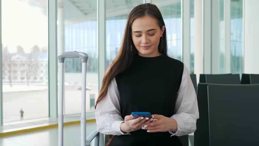 Cute young traveler woman or college student using mobile phone call at airport terminal with luggage. Study or travel abroad, international tourism or telephone communication technology concept | Shutterstock HD Video #1010157986