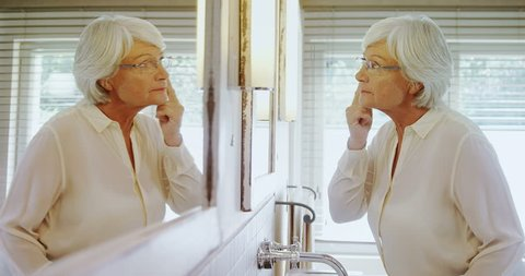 Senior caucasian woman looking at herself in mirror at home 4k