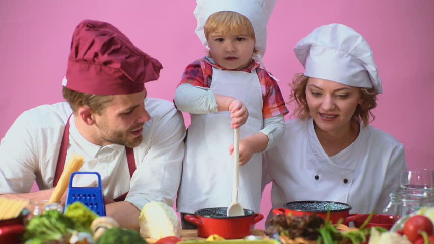 Cute little boy and his beautiful parents are smiling while cooking in kitchen. Young family cooking food in kitchen. Happy family cooking together. Happy young family with Mum, Dad child cooking.   Shutterstock HD Video #1010186636