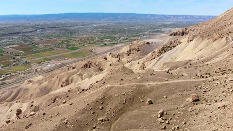 Green agricultural land and desert meet in the Grand Valley. Filmed by a drone near the Boockliff Mountains in Palisade, Colorado. Looking West from Mount Garfield.