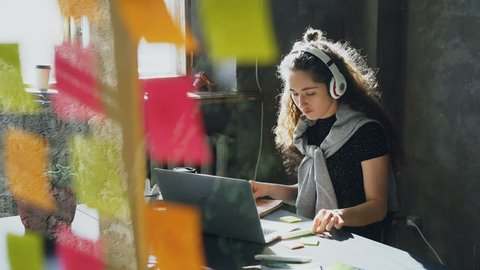 Creative young businesswoman is listening to music in headphones dancing and singing while working at desk with laptop in modern office. Glass with colored stickers in foreground.