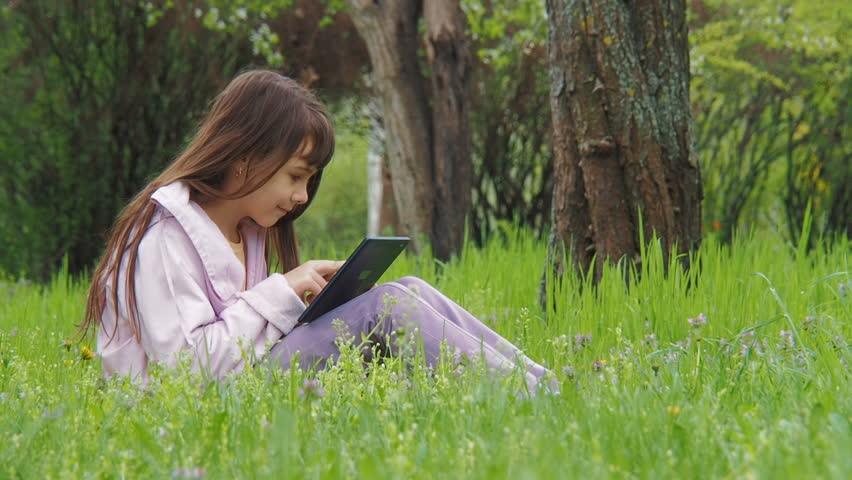 Child with a tablet. Girl on the nature on the Internet. | Shutterstock HD Video #1010215466