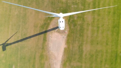 Aerial view of a rotating wind generator in a green field during the day. Electricity generation. The drone flies by next to the turbine. The windmill is close-up. Modern technologies.