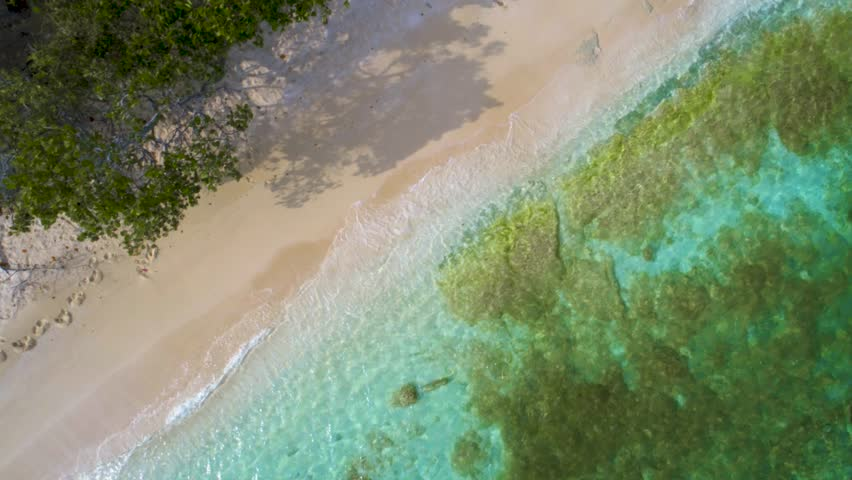 Bird's eye view of waves and sand over a Caribbean cay with turquoise waters | Shutterstock HD Video #1010224556