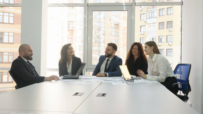 Office workers, employees of a large company, two young men and three young women sitting at a table discussing all the company's questions, the end of the meeting, all employees are happy and smiling | Shutterstock HD Video #1010229326