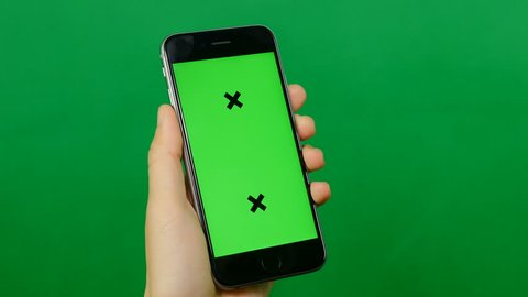 Businesswoman holds a blank green screen mobile phone on green background. Front view.