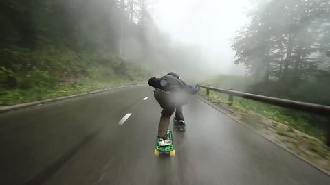 pov longboarder extreme fast downhill on slippery rainy mountain road,show tucking and sliding techniques