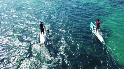April 2018: Aerial drone video of competition sport paddle surfing or sup between 2 men in tropical Caribbean sea
