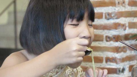 Asian cute girl enjoy eating soup. Family enjoy eating Shabu Shabu hotpot in restaurant. Healthy food concept.