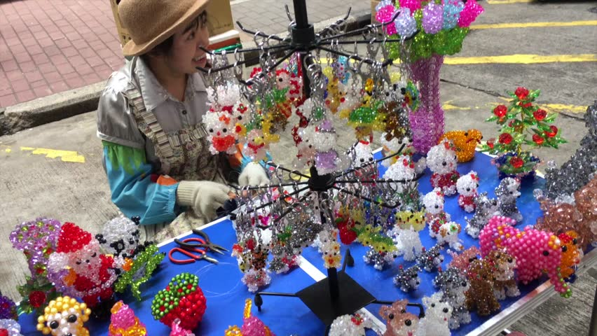 HONG KONG - SEPT 2017: An unidentified woman makes gifts and souvenirs from plastic beads and sells them in Broadway district.