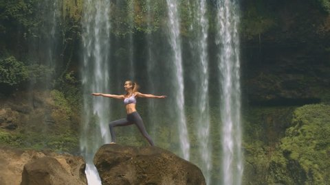 side view young beautiful woman does yoga exercise on large rock against pictorial waterfall