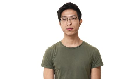 Portrait of serious asian man wearing glasses and basic t-shirt touching his chin and thinking or remembering, isolated over white background. Concept of emotions