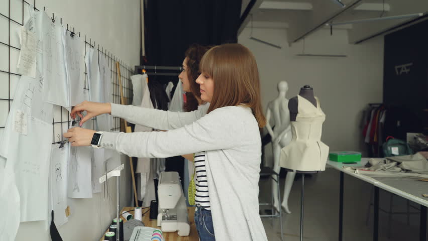 Attractive women clothing designers looking at garment sketches hanging on wall, discussing them, choosing new images for newest collection. Friendly informal atmosphere. | Shutterstock HD Video #1010290316