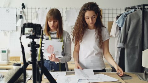 Young women fashion bloggers recording video blog about ladies'clothes on camera and talking to followers in modern studio. Many garment sketches are visible.