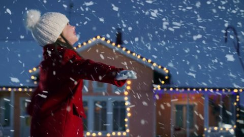 Cute Little Girl Dances in the Falling Snow. Child Enjoys Winter Weather. Having Fun One Winter Evening In the Background of the House Decorated with Garlands and Christmas Tree. Shot on RED EPIC-W 8K