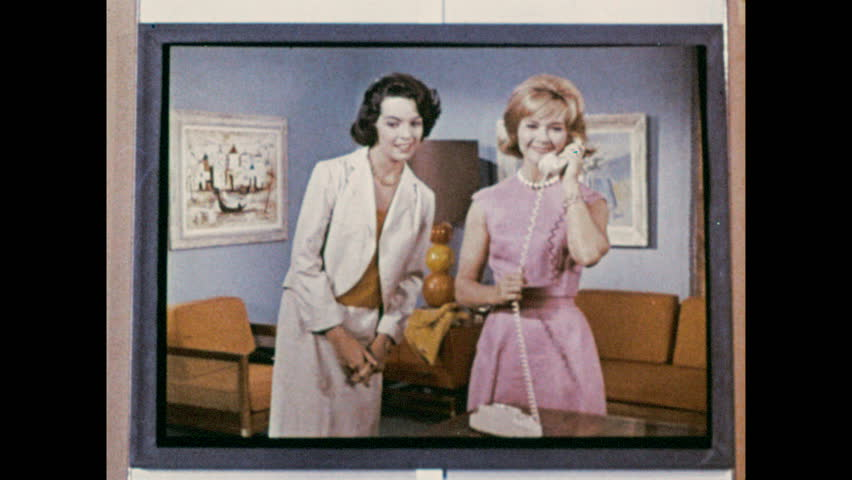 1960s: Image on screen, woman hands phone to other. Close up of woman talking. Image on screen, she is on phone, zoom out to woman at desk. #1010314016