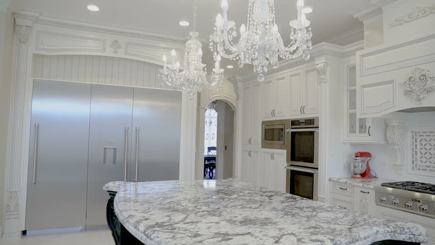 Luxurious white kitchen in a new home with a marble table
