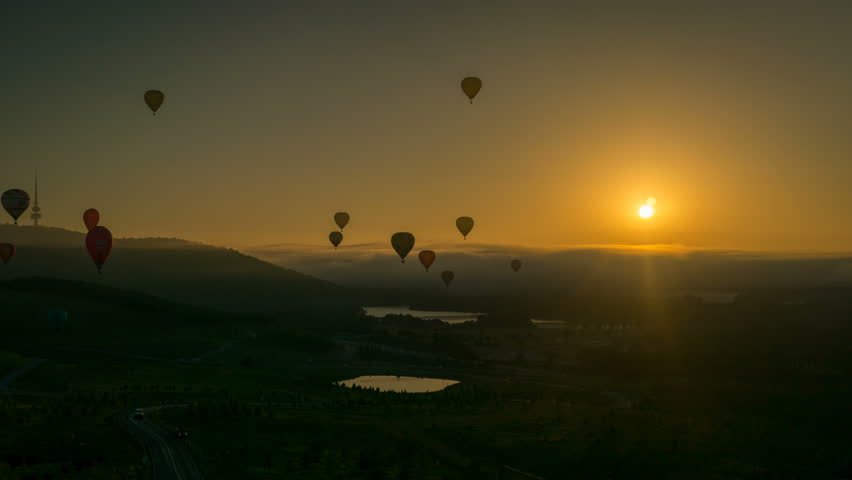 Silhouette time lapse of hot air balloons at sunrise flying over beautiful landscapes in Canberra, Australia.