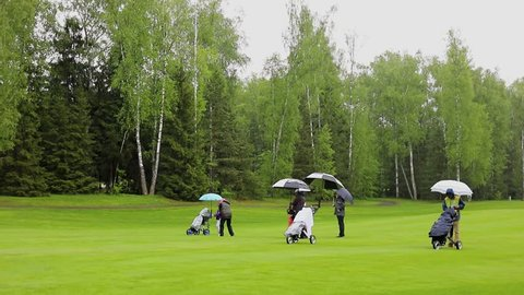 Player makes shot during golf match on field at summer rainy day. Slow motion