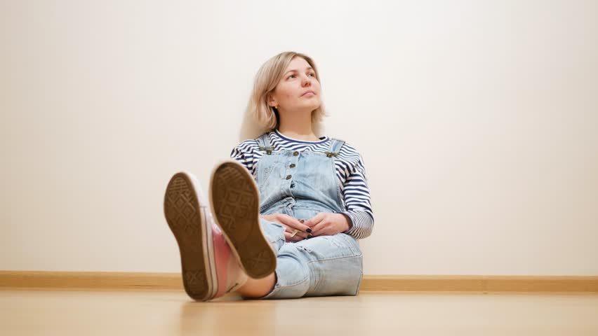 Young woman sitting near wall in empty flat and dreaming | Shutterstock HD Video #1010329436