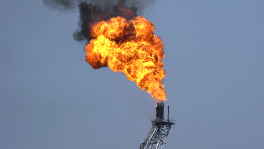 Fire on flare stack at offshore oil and gas central processing platform while burning toxic and release over pressure from process emergency shut down. 4K footage with environment sound.