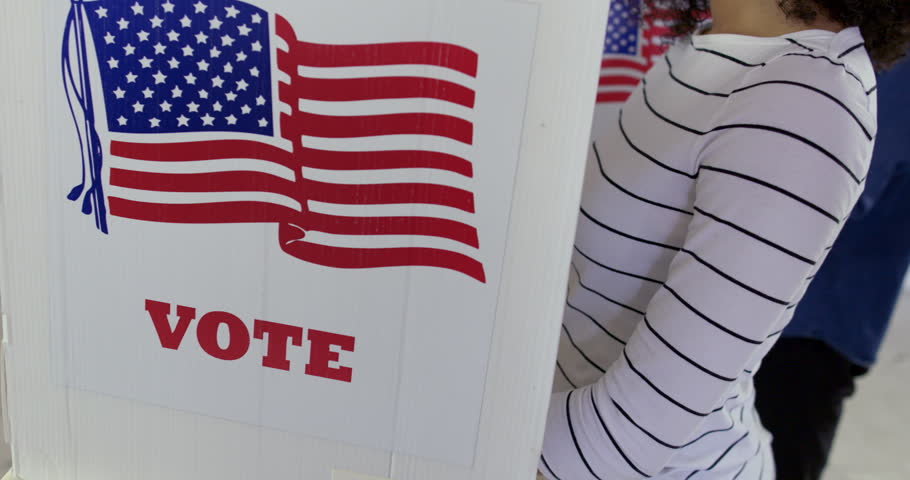 Close up, camera moves from voting booth up to young Latina woman casting vote at polling station. Other voters in background and large US flag on wall behind. Hand held, slow motion 4K 60fps | Shutterstock HD Video #1010344106