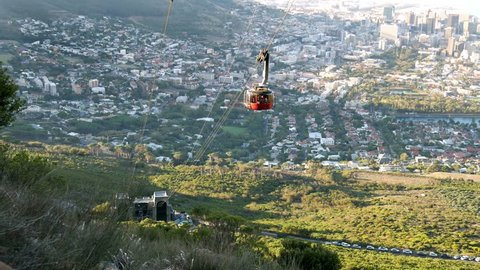 Cape Town Table mountain descending cable car approaching bottom station with city panoramic view below & green mountain slopes