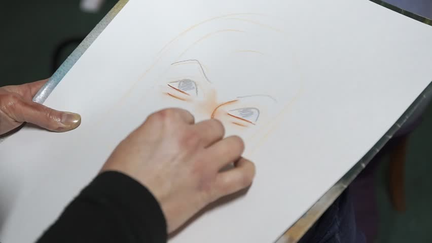 A woman paints a cartoon portrait of chalk on paper. Close-up only hands. Grotesque, parody | Shutterstock HD Video #1010369216