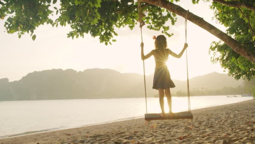 Little girl swinging on a swing on the beach at sunset. 4K