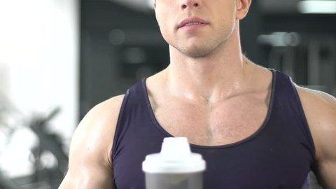 Bodybuilder drinking protein shake for muscle gain, sport bar, healthy diet