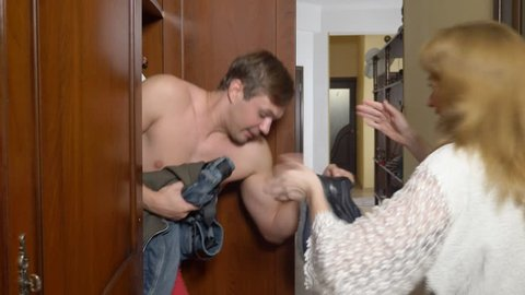 a woman hides her lover in a closet from her husband. the naked man is hiding in the wardrobe. he goes out of the closet and runs away from the mistress's house through the front door. 4k,
