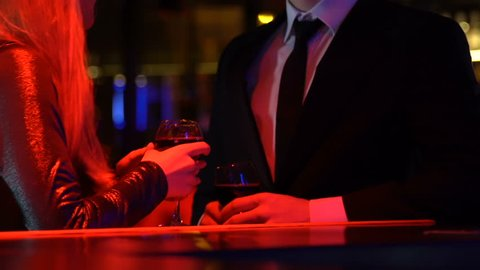 Young woman flirting with man in night club, couple enjoying date with wine