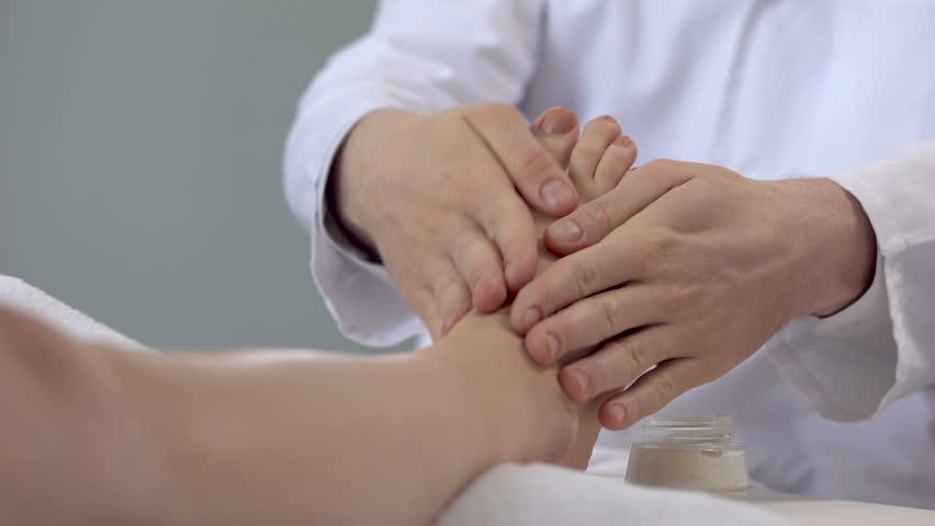 Specialist doing feet massage using cream, cosmetology procedures, beauty salon | Shutterstock HD Video #1010429936