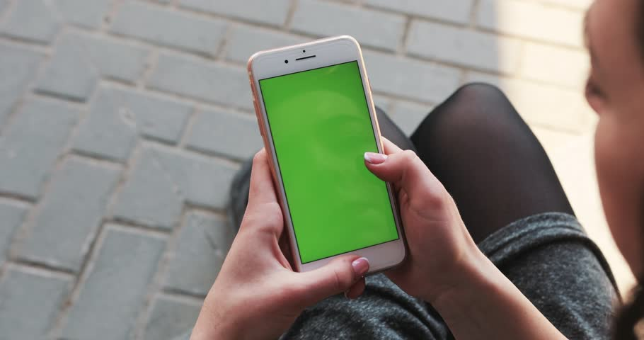 NEW YORK - April 5, 2018:Close up hands woman holding use white phone with green screen busy sitting on street scrolling pages swiping surfing internet technology smartphone message mobile phone #1010457716