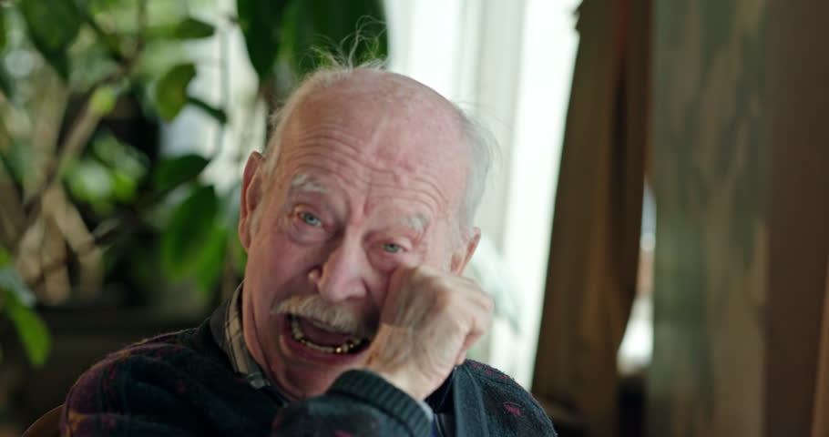 Portrait of casual elderly man sitting on chair and smiling happily at camera at home. | Shutterstock HD Video #1010469026