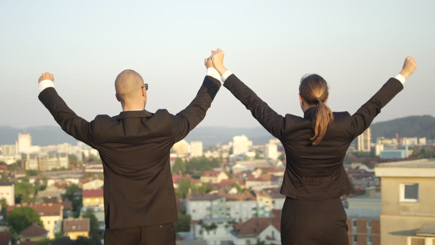 SLOW MOTION, CLOSE UP, DOF: Successful businessman and businesswoman standing on the edge of tall skyscraper on sunny day and raising hands high in the air after concluding important financial deal | Shutterstock HD Video #1010488706