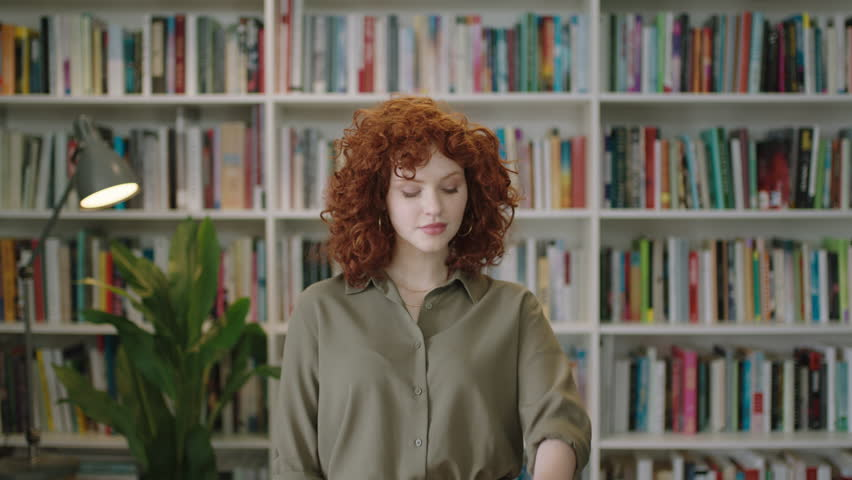portrait of lovely young librarian woman standing in library texting attractive student smiling close up red head using smart watch