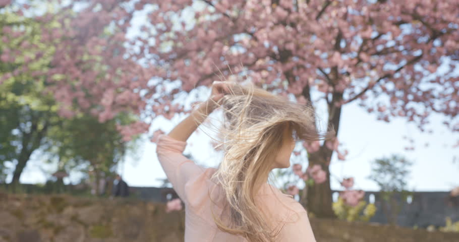Happy pretty blonde girl with moving from wind hair is actively dancing and spinning round in the blooming sakura garden. 4k footage.
