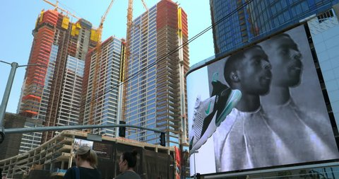 LOS ANGELES, CALIFORNIA, USA - APRIL 22, 2018: Construction boom at development site and people walking near famous NBA Staples Center, palm trees and electronic digital billboards in Los Angeles, 4K
