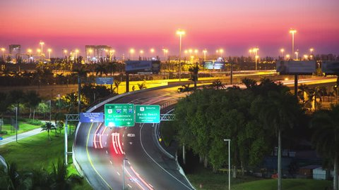 Ft. Lauderdale Florida Interstate Traffic Timelapse during Early Morning Dawn with Moving Lights from Cars Driving near FLL Hollywood International Airport in front of a Vibrant Colored Sky