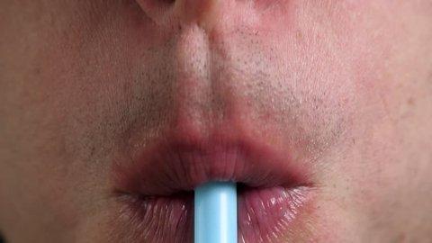Man drink unpalatable beverages through blue straw. Closeup on lips